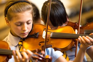 Close-up of Primary girl playing the violin.