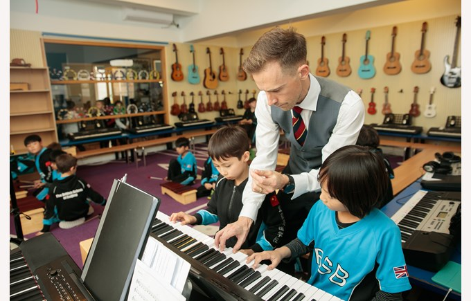 Class learning to play the piano.