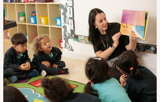 A view of an Early Years classroom with teacher and students listening intently.