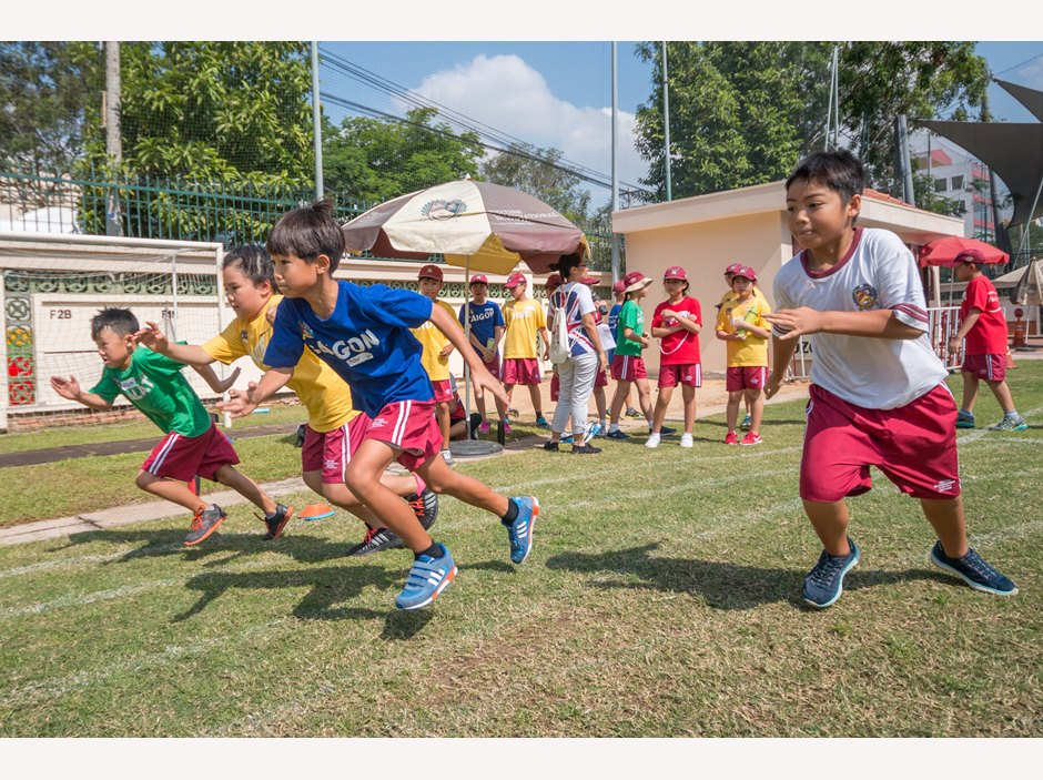 TX students running on grass playing field