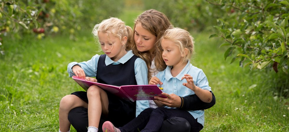 three international school students reading in the orchard - La Cote, Aubonne