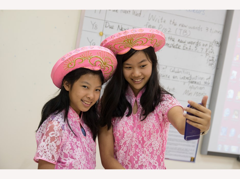 Two girls in Ao Dai taking selfie