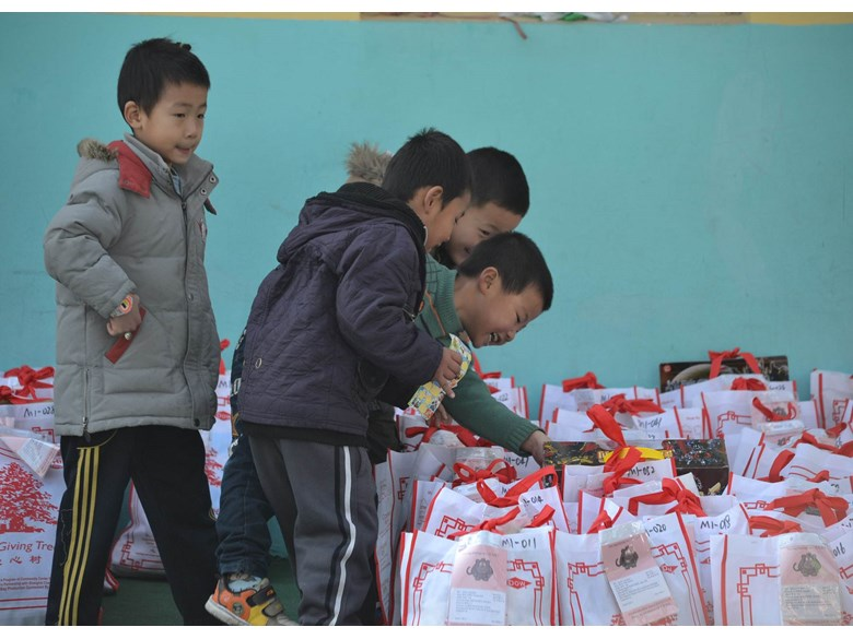 Chinese Migrant children excited about the gifts they receive from the Giving Tree project