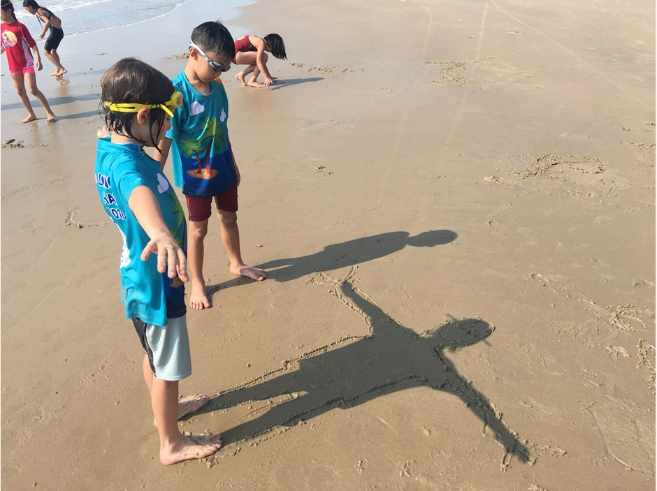 Kids looking at their shadow on the seaside