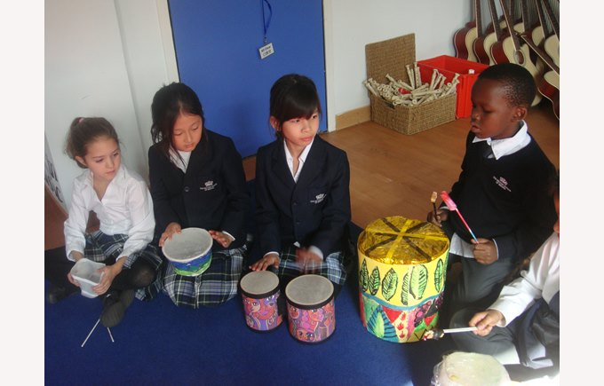A group of Year 4 students drumming with their own djembe drums made with found materials.