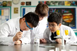 3 boys in the science lab doing an experiement