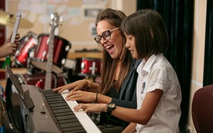 Child learning to play piano in music lessons