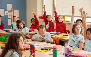 Interested children raise their hands to answer a question in the classroom.