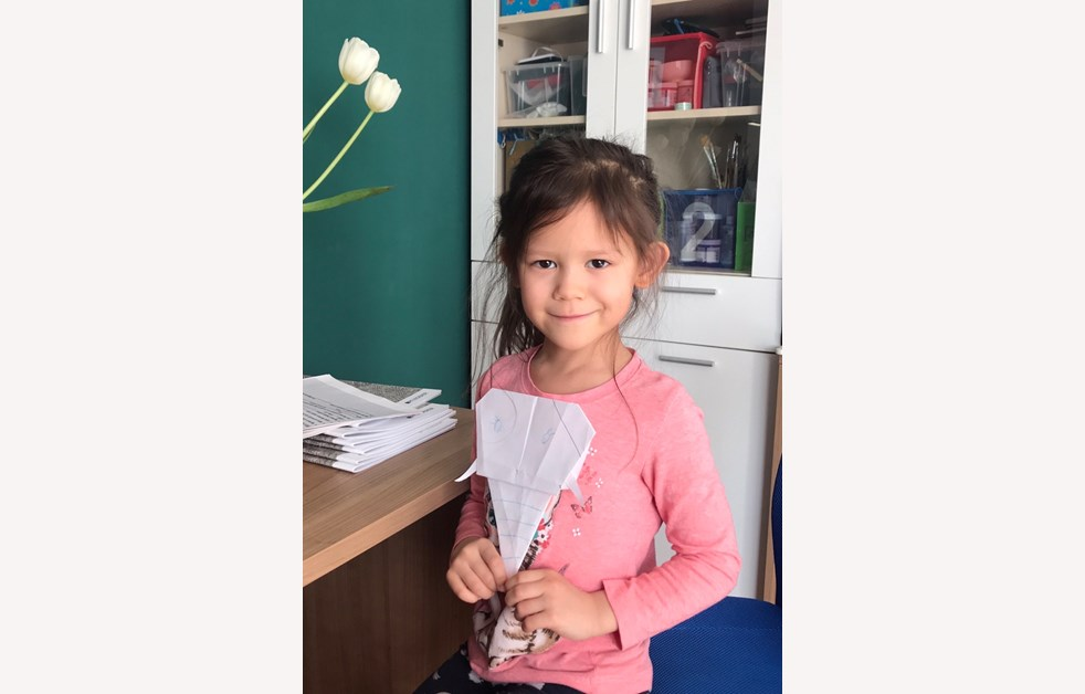 Elli following instructions in an English task to make a paper elephant
