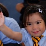 Primary student raising hand in class