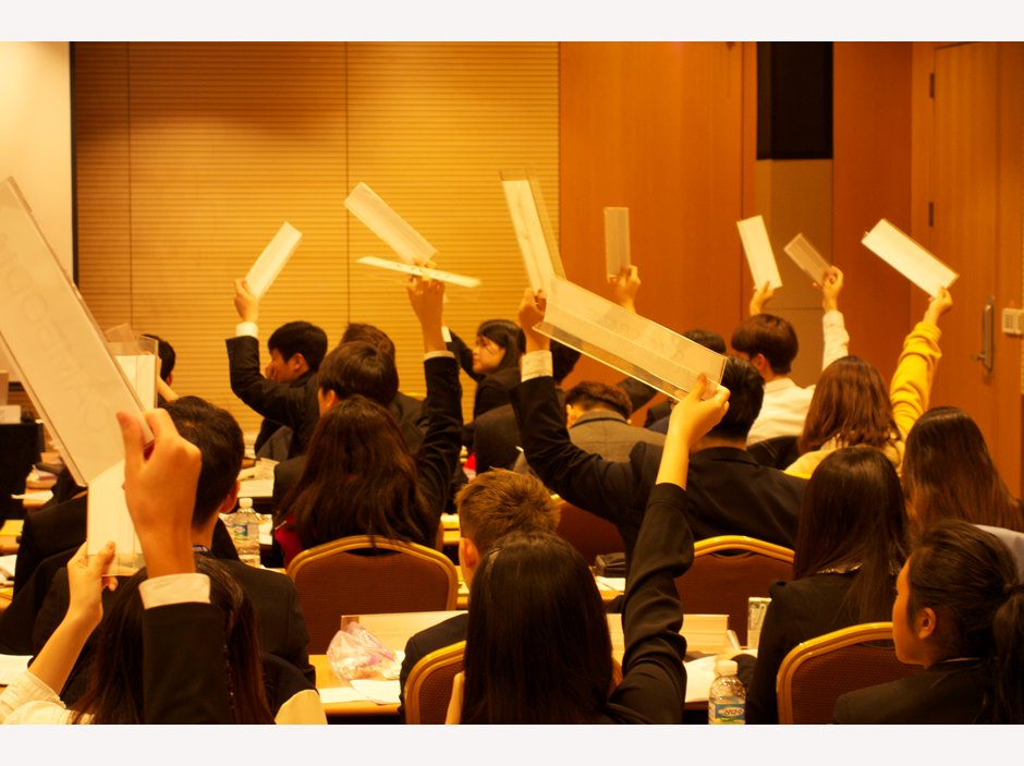 Students raise their hands to vote at Seoul Model United Nations 2015