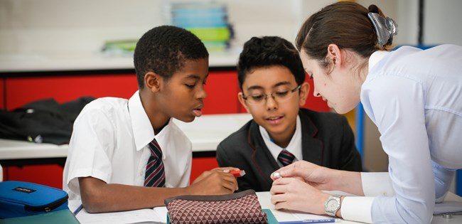 secondary science teacher helping students