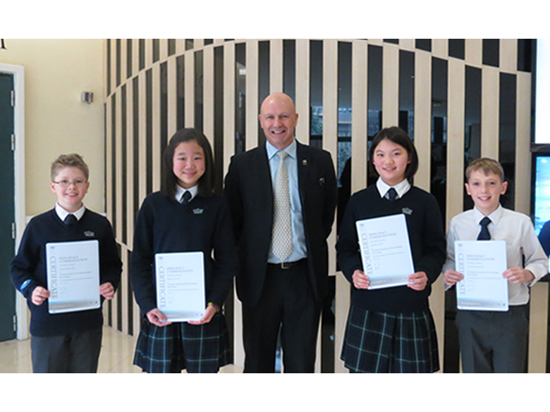 Kevin Foyle presenting Principal's Commendations to students at the British International School Shanghai, Puxi