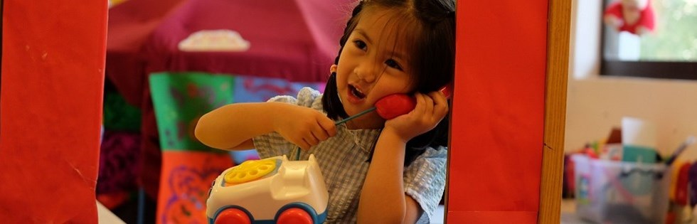Early Years student on toy telephone