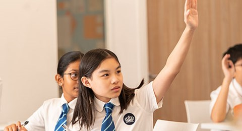 A secondary student raises her hand in class.