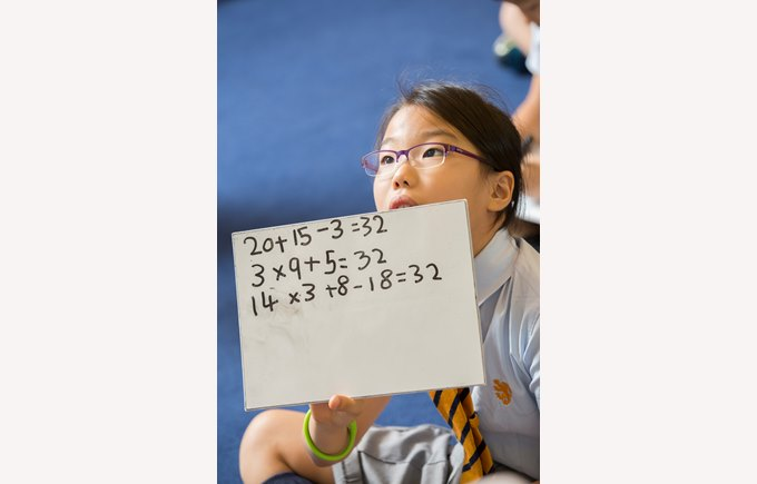 A Primary student showing her math work to the teacher.