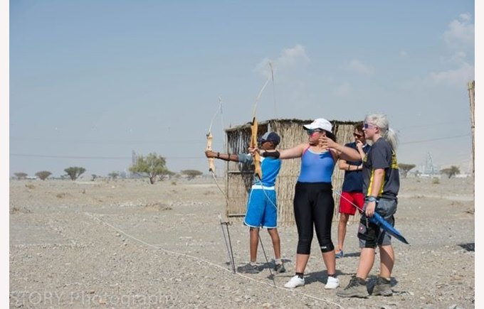 Children at archery practice in the desert