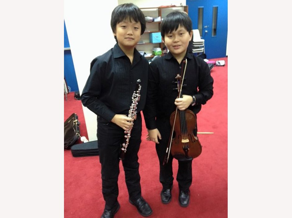 2 BIS boys taking photo before FOBISIA Orchestral Festival