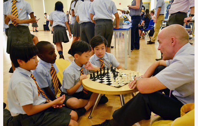 The Principal playing chess with Primary students.