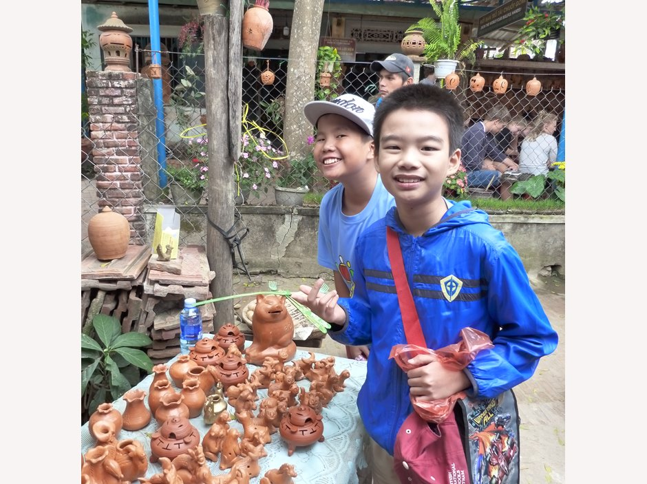 Two boys smiling next to handmade toy counter