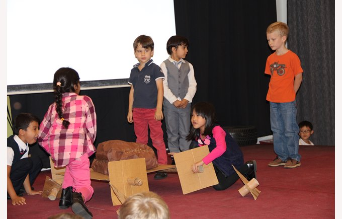 The children are making a car with props on a stage during the performance.