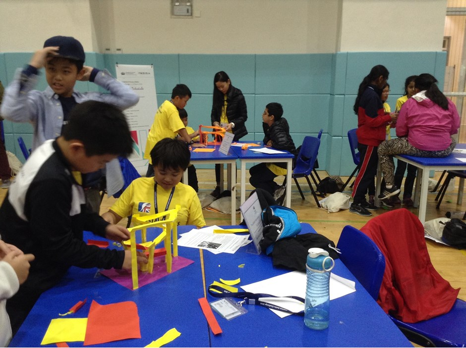 Students gathering in group cutting and pasting paper
