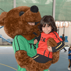 Child being cuddled by a mascot