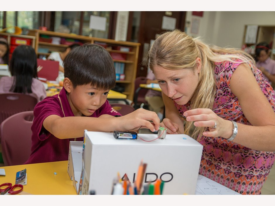 Image of teacher helping a Primary student during Science week