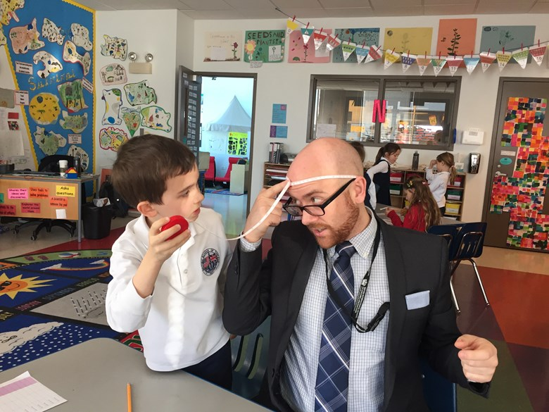 Science teacher Tom Collins holds measuring tape for grade 2 student in a lesson on using standard measuring units.