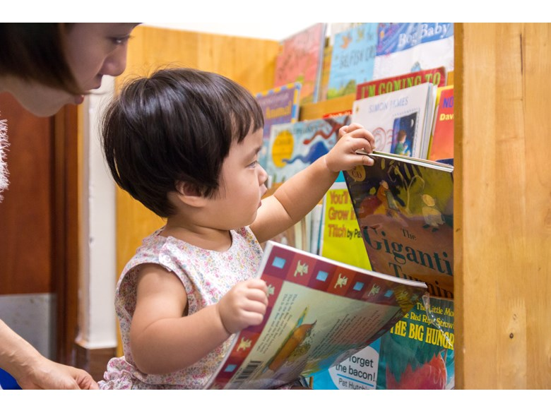 Young toddler choosing books