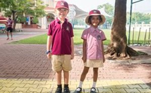 Two primary school children wearing full uniform