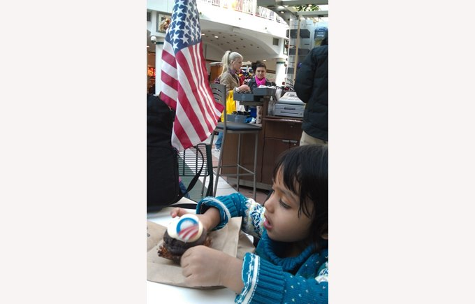An american-indian girl eating an Obama-campaign cupcake after the inauguration.