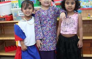 Three EYFS kids in traditional costume in TX International Week