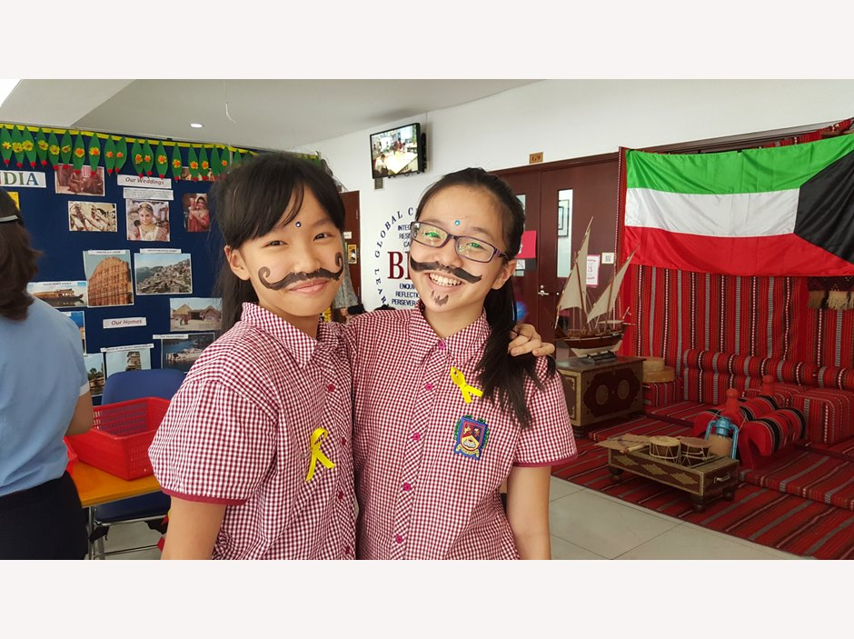 Two students with painted beards in TX International Week