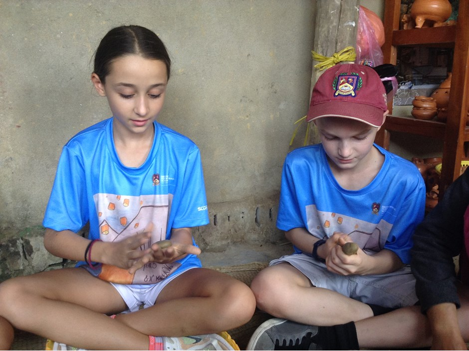 Two students learning how to form the clay into shape
