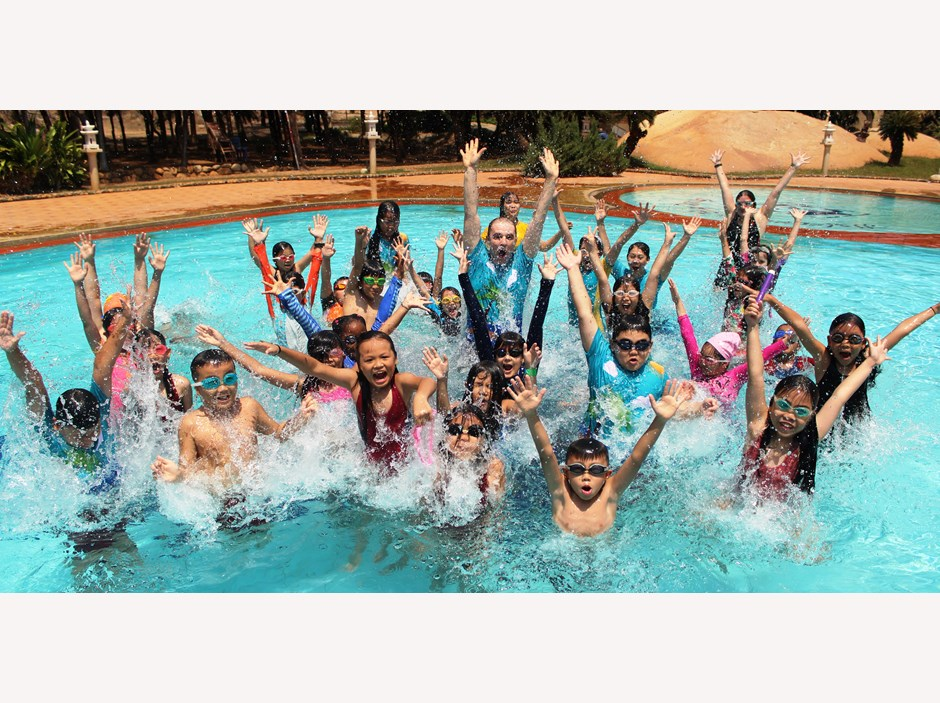 Kids raising their hands in the swimming pool
