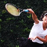 Secondary tennis player serves on court