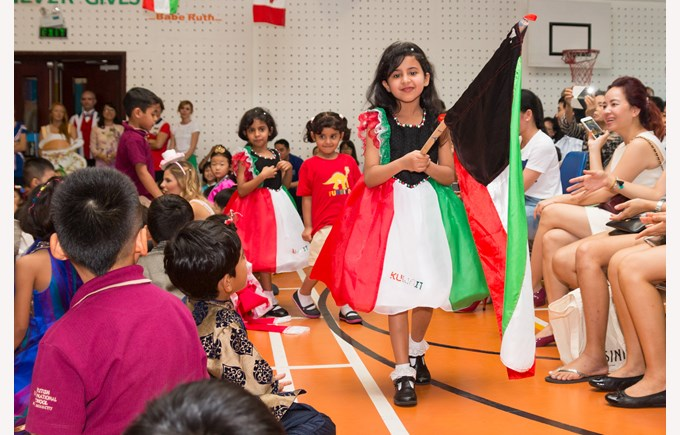 Student holding Kuwait flag in TX International parade