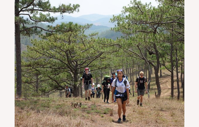 Student hiking with several students in the background on an IA trip in Dalat