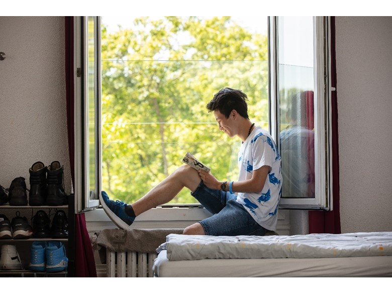 A boy sits at his dorm bedroom window reading