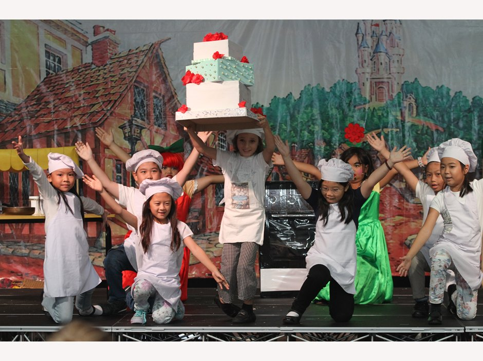 One girls holding a big cake while others dancing in TX MP2 Production
