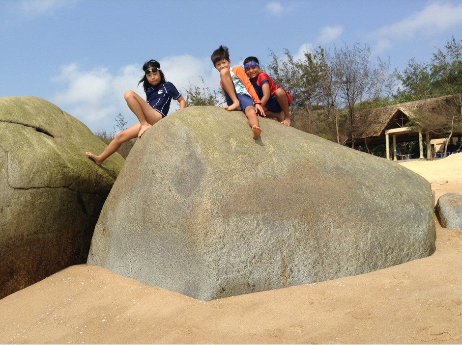 Three kids sitting on a big rock