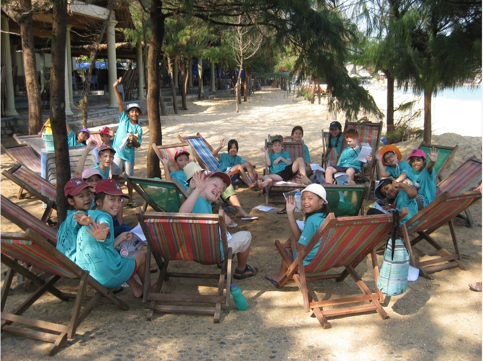 A group of students sitting on wooden chairs