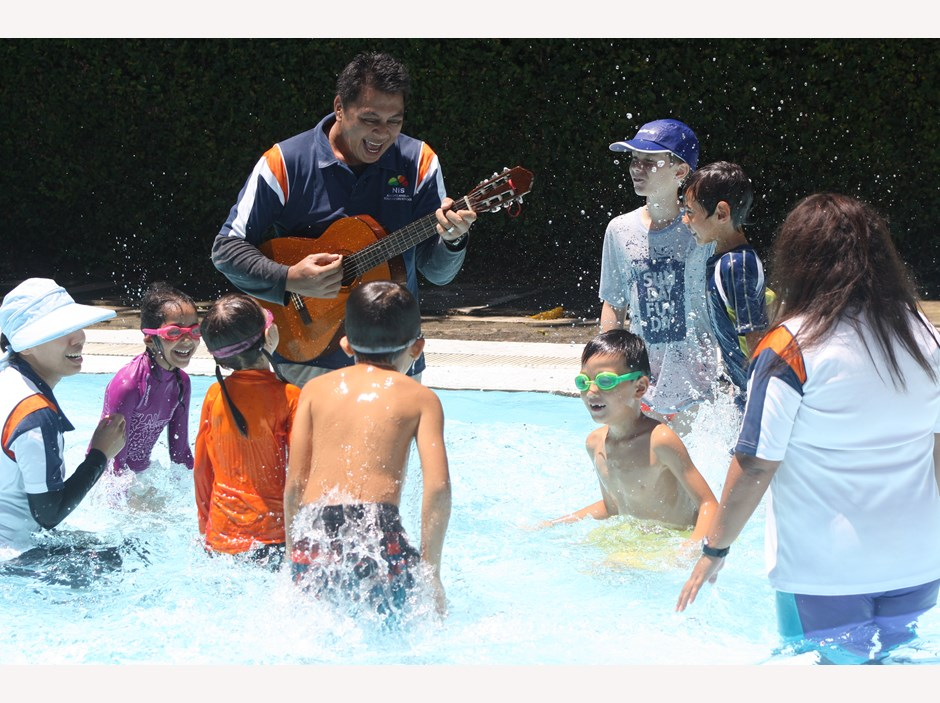 teacher and students singing in the pool