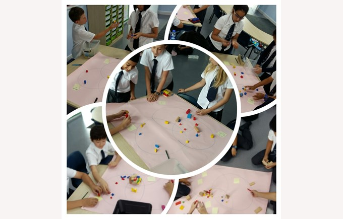 Year 6 mathematicians work together to categorise 3D shapes