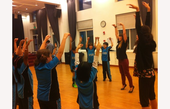 Theatre workshop group exercise stretching arms above heads on toes.