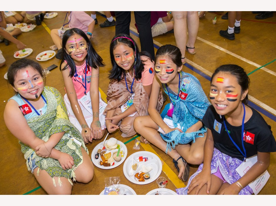 Five girls with painted faces enjoying food