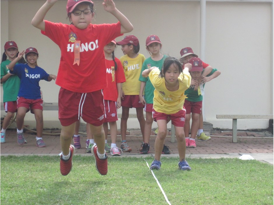 Two girls competing in long jump competition