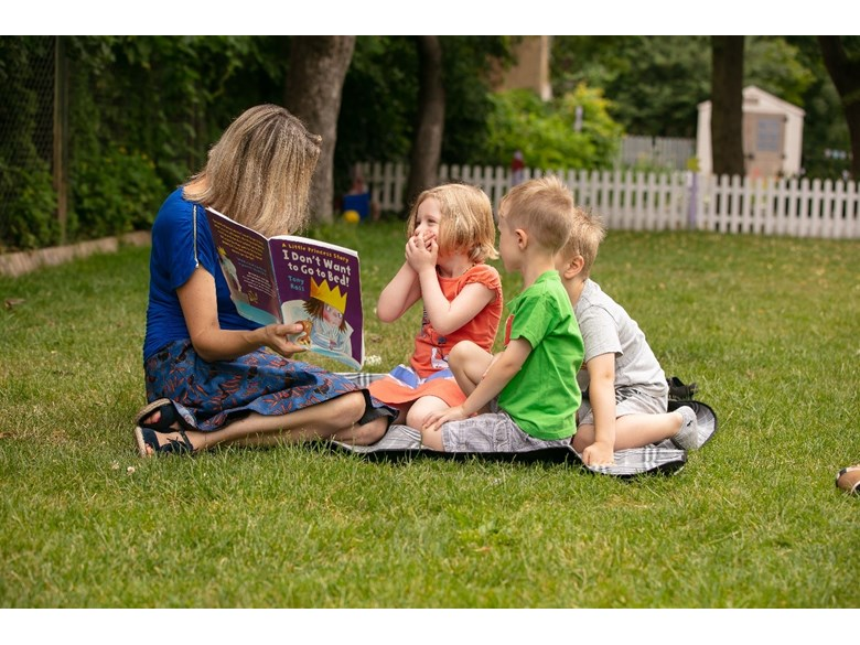 An adult reads a book to three children