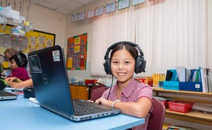 Primary student sitting with headphones and computer